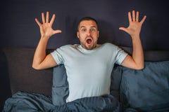 Ο αναρωτημένος νεαρός άνδρας κάθεται στο κρεβάτι και κοιτάζει κατευθείαν στη κάμερα Κρατά τα χέρια του επάνω Ο τύπος είναι φοβησμ στοκ εικόνα με δικαίωμα ελεύθερης χρήσης