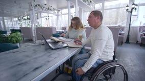 Ο ανεξάρτητος επιχειρηματίας είναι εκτός λειτουργίας στην αναπηρική καρέκλα με τη γυναίκα που χρησιμοποιεί την έξυπνη τεχνολογία  απόθεμα βίντεο