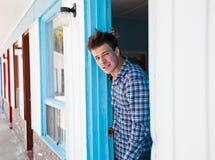 Ο νεαρός άνδρας κοιτάζει από το δωμάτιο μοτέλ στοκ εικόνα