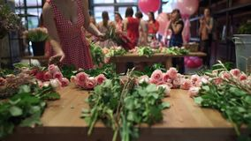 Ο ανθοκόμος γυναικών τακτοποιεί τα λουλούδια στον πίνακα απόθεμα βίντεο
