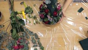 Ο ανθοκόμος κάνει μια κωνική μορφή τη φρέσκια ρύθμιση λουλουδιών στο floral αφρό απόθεμα βίντεο