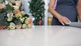 Ο ανθοκόμος κυλά ένα έγγραφο για τον πίνακα για να τυλίξει την ανθοδέσμη των τριαντάφυλλων, άποψη κινηματογραφήσεων σε πρώτο πλάν απόθεμα βίντεο