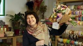 Ο ανθοκόμος παρουσιάζει στους πελάτες της ολοκληρωμένη ανθοδέσμη των λουλουδιών απόθεμα βίντεο