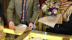 Ο ανθοκόμος τυλίγει μια ανθοδέσμη των λουλουδιών σε ένα όμορφο τυλίγοντας έγγραφο απόθεμα βίντεο