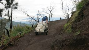 Ο ανθρακωρύχος τραβά ένα κάρρο από την κορυφή του ενεργού ηφαιστείου Ka στοκ εικόνα με δικαίωμα ελεύθερης χρήσης