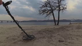 Ο ανιχνευτής μετάλλων στις όχθεις του ποταμού ψάχνει τα κοσμήματα θησαυρών στην άμμο στην παραλία στα πλαίσια του bri απόθεμα βίντεο