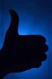 Ο αντίχειρας σκιαγραφεί επάνω με το γαλαζωπό υπόβαθρο Στοκ φωτογραφία με δικαίωμα ελεύθερης χρήσης