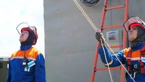 Ο ανταγωνιστής στην εξάρτηση φαίνεται ανοδικός τραβά το σχοινί ενάντια στη σκάλα από τον τοίχο απόθεμα βίντεο