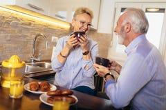 Ο ανώτεροι άνδρας και η γυναίκα συνδέουν τη συνεδρίαση μαζί στο σπίτι που χαμογελά και που πίνει το τσάι ή τον καφέ στοκ φωτογραφία με δικαίωμα ελεύθερης χρήσης