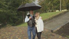 Ο ανώτερος άνδρας περπατά με τη νέα γυναίκα κατά τη διάρκεια της βροχής στο πάρκο, γάμος της ευκολίας απόθεμα βίντεο