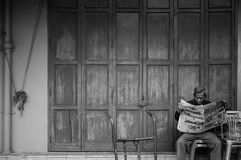 Ο ανώτερος ασιατικός ηληκιωμένος κάθεται την εφημερίδα ανάγνωσης μπροστά από το παλαιό vint στοκ εικόνες
