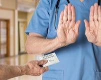 Ο ανώτερος γιατρός τρίβει μέσα την άρνηση της κάρτας Medicaid στοκ εικόνες με δικαίωμα ελεύθερης χρήσης