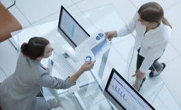 Ο ανώτερος διευθυντής μεταβιβάζει στον υπάλληλο το οικονομικό έγγραφο Στοκ Εικόνα