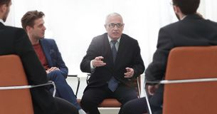 Ο ανώτερος επιχειρηματίας πραγματοποιεί μια συνεδρίαση με την επιχειρησιακή ομάδα Στοκ Εικόνες