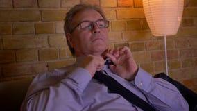 Ο ανώτερος επιχειρηματίας στο πουκάμισο χαλαρώνει επάνω το δεσμό μετά από τη σκληρή εργάσιμη ημέρα που κουράζεται και που εξαντλε απόθεμα βίντεο