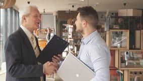 Ο ανώτερος επιχειρηματίας υποβάλλει μερικές ερωτήσεις στο νεώτερο συνεργάτη του στοκ εικόνες με δικαίωμα ελεύθερης χρήσης