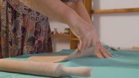 Ο ανώτερος θηλυκός αγγειοπλάστης κυλά τον άργιλο όπως μια ζύμη απόθεμα βίντεο