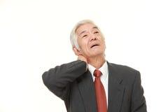 Ο ανώτερος ιαπωνικός επιχειρηματίας πάσχει από τον πόνο λαιμών Στοκ φωτογραφία με δικαίωμα ελεύθερης χρήσης