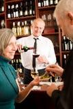 Ο ανώτερος μπάρμαν ζευγών ράβδων κρασιού χύνει το γυαλί Στοκ Εικόνες
