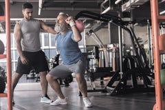Ο ανώτερος συνταξιούχος έχει workout με τον εκπαιδευτικό στο αθλητικό κέντρο στοκ εικόνες