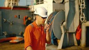 Ο ανώτερος υπάλληλος γεφυρών στη γέφυρα του παράκτιου σκάφους κρατά walkie-talkie VHF το ραδιόφωνο φιλμ μικρού μήκους