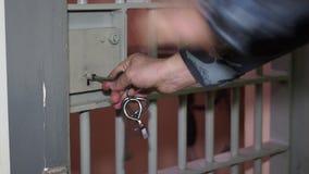 Ο ανώτερος υπάλληλος φυλακών ανοίγει τη σχάρα και την πόρτα της κάμερας με τα κλειδιά στη ρωσική κινηματογράφηση σε πρώτο πλάνο φ απόθεμα βίντεο