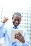 Ο ανώτερος υπάλληλος γιορτάζει την επιτυχία του που κρατά μια ταμπλέτα Στοκ Εικόνες