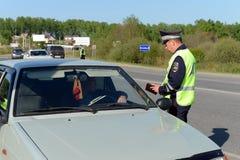 Ο ανώτερος υπάλληλος της αστυνομίας ελέγχει τα έγγραφα του οδηγού του αυτοκινήτου Στοκ φωτογραφία με δικαίωμα ελεύθερης χρήσης