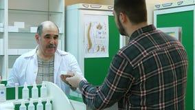Ο ανώτερος φαρμακοποιός και ο νέος αρσενικός πελάτης έχουν τη σύγκρουση στο φαρμακείο στοκ εικόνα