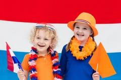 Ολλανδικά παιδιά Παιδιά με τη σημαία των Κάτω Χωρών Ανεμιστήρες της Ολλανδίας Στοκ Εικόνες