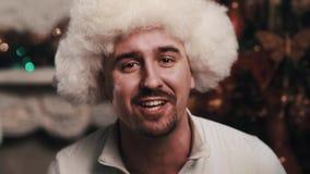 Ο αοιδός Unshaved στο καπέλο γουνών εκτελεί τη συνεδρίαση στο δωμάτιο με τις διακοσμήσεις Χριστουγέννων φιλμ μικρού μήκους