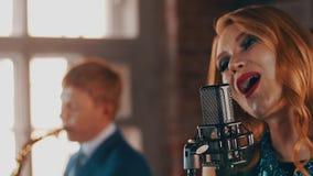 Ο αοιδός με τα κόκκινα χείλια αποδίδει στη σκηνή στο μικρόφωνο με την κομψότητα saxophonist απόθεμα βίντεο