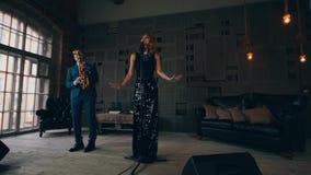 Ο αοιδός της Jazz στο καμμένος φόρεμα που αποδίδει στη σκηνή με το saxophonist αυξάνει τα χέρια απόθεμα βίντεο