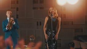 Ο αοιδός της Jazz στο φόρεμα έντονου φωτός και το saxophonist στο μπλε κοστούμι αποδίδουν στη σκηνή ντουέτο απόθεμα βίντεο