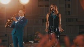 Ο αοιδός της Jazz στο χορό φορεμάτων έντονου φωτός τραγουδά στη σκηνή με το saxophonist στο μπλε κοστούμι φιλμ μικρού μήκους
