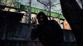 Ο απαίσιος θεριστής ή ο άγγελος του θανάτου στο ΒΙΟΜΗΧΑΝΙΚΟ ΑΣΤΙΚΟ ΤΟΠΙΟ πηγαίνει στη κάμερα και κλείνει το φακό με το χέρι απόθεμα βίντεο