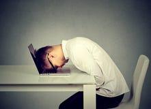 Ο απελπισμένος υπάλληλος τόνισε το στηργμένος κεφάλι νεαρών άνδρων στο πληκτρολόγιο lap-top στοκ εικόνα