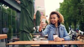 Ο απρόσεκτος ευτυχής τουρίστας γυναικών αφροαμερικάνων παίρνει selfie με το smartphone στην υπαίθρια συνεδρίαση καφέδων στον πίνα απόθεμα βίντεο