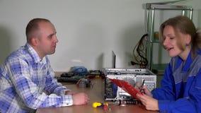 Ο απρόσεκτος θηλυκός ειδικός επισκευής υπολογιστών δίνει επισκευασμένο τον πελάτης υπολογιστή ταμπλετών απόθεμα βίντεο