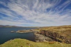 Ο απότομος βράχος θάλασσας με το χαμηλό ακρωτήριο στο υπόβαθρο και το μπλε ουρανό με άσπρα cirrus καλύπτει Στοκ Εικόνες