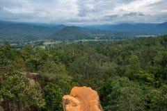 Ο απότομος βράχος του πορτοκαλιού εδαφολογικού βουνού στο δάσος με τη νεφελώδη άποψη ουρανού στοκ εικόνες με δικαίωμα ελεύθερης χρήσης