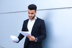 Ο αραβικός επιτυχής επιχειρηματίας κρατά τα έγγραφα, χαμογελώντας το λίγο s Στοκ Εικόνα