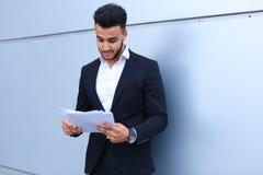 Ο αραβικός επιτυχής επιχειρηματίας κρατά τα έγγραφα, χαμογελώντας το λίγο s Στοκ φωτογραφίες με δικαίωμα ελεύθερης χρήσης