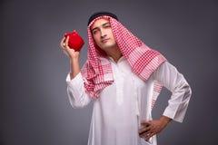 Ο αραβικός επιχειρηματίας με το piggybank στο γκρίζο υπόβαθρο Στοκ εικόνες με δικαίωμα ελεύθερης χρήσης