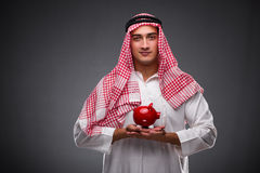 Ο αραβικός επιχειρηματίας με το piggybank στο γκρίζο υπόβαθρο Στοκ Φωτογραφίες
