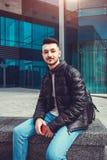 Ο αραβικός σπουδαστής με ένα σακίδιο πλάτης και ένα τηλέφωνο χαλαρώνει έξω Το άτομο εξετάζει το τηλέφωνο μπροστά από το σύγχρονο  Στοκ Εικόνες