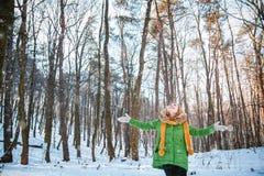 Ο αριθμός ενός κοριτσιού σε μια ζακέτα, καπέλο, χνουδωτά γάντια, που στέκεται με τα όπλα, που αντιμετωπίζουν τον ήλιο το χειμώνα στοκ εικόνες