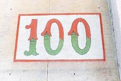Ο αριθμός 100 χρωμάτισε σε ένα κτήριο Στοκ Φωτογραφίες