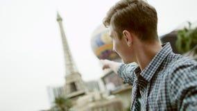 Ο αριστοκρατικός τύπος κρατά τη κάμερα μπροστά από τον και δείχνει στον πύργο του Άιφελ στο Λας Βέγκας απόθεμα βίντεο