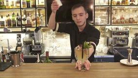 Ο αριστοκρατικός bartender μπάρμαν εξυπηρετεί το σαφές κλασικό ρούμι που βασίζεται πίνει το δονητή διακοσμήσεων ασβέστη κοκτέιλ σ φιλμ μικρού μήκους